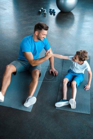 Photo pour Vue aérienne d'un père heureux et de son fils tenant la main sur un tapis de conditionnement physique - image libre de droit