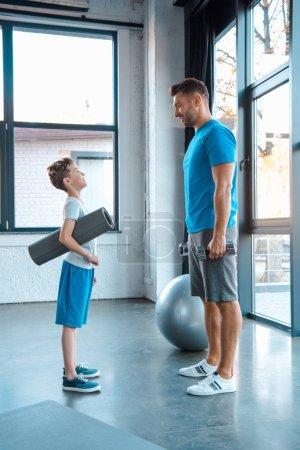 Photo pour Vue latérale d'un enfant regardant son père debout avec un tapis de conditionnement physique dans un gymnase - image libre de droit