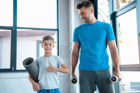 Photo for Happy father holding dumbbells near cute son showing thumb up  in gym - Royalty Free Image