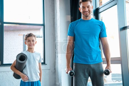 Photo for Happy father holding dumbbells near cute son with fitness mat - Royalty Free Image