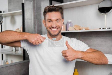 Photo pour Homme gai en t-shirt blanc tenant brosse à dents et montrant pouce dans la salle de bain - image libre de droit