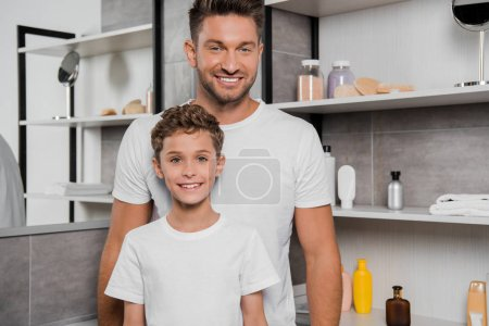 cheerful father and son smiling in bathroom
