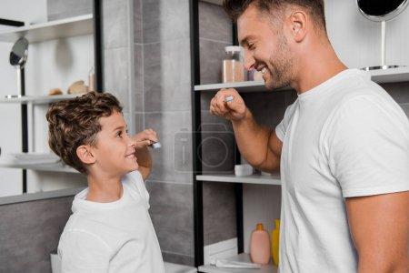 Photo pour Heureux enfant tenant brosse à dents et regardant père dans la salle de bain - image libre de droit