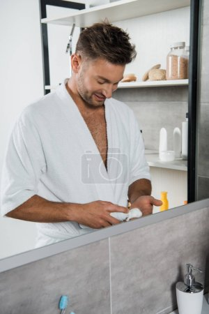 Photo pour Homme gai tenant peut avec mousse à raser dans la salle de bain près du miroir - image libre de droit