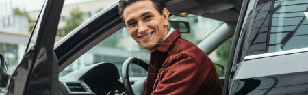 Photo for Taxi driver sitting in car with open door and smiling at camera, panoramic shot - Royalty Free Image