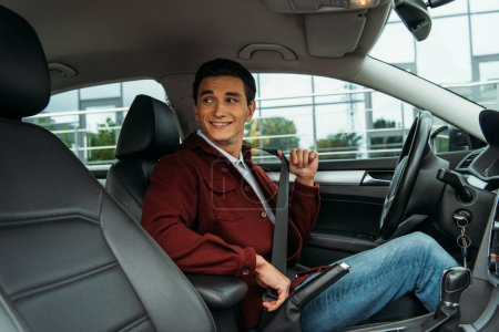 Photo for Smiling man holding safety belt in car and looking away - Royalty Free Image