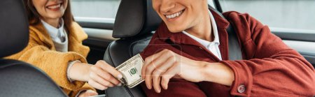 Photo for Cropped view of passenger paying off with smiling taxi driver, panoramic shot - Royalty Free Image