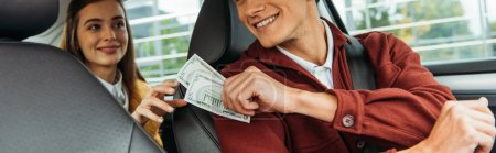 Photo for Cropped view of passenger paying off with taxi driver, panoramic shot - Royalty Free Image