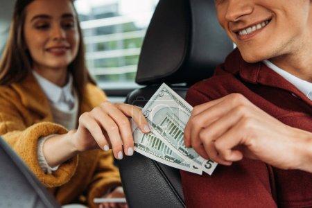Photo pour Concentration sélective du passager donnant des billets en dollars au chauffeur de taxi - image libre de droit