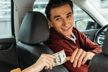 Photo for Smiling taxi driver taking cash from woman hand - Royalty Free Image