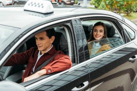 Photo for Woman passenger smiling at camera while man driving taxi - Royalty Free Image
