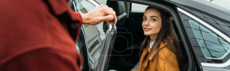 Photo for Over shoulder view of taxi driver opening car door for woman, panoramic shot - Royalty Free Image