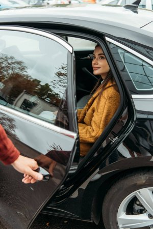 Photo for Smiling woman passenger while taxi driver opening car door - Royalty Free Image