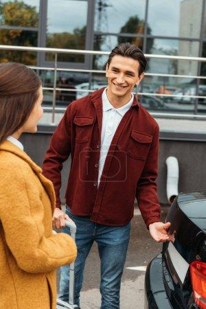 Photo pour Chauffeur de taxi tenant une valise et souriant à la femme par le coffre de la voiture - image libre de droit