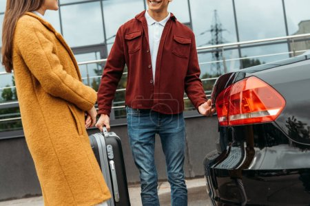 Photo for Cropped view of taxi driver holding suitcase and smiling to passenger by car trunk - Royalty Free Image