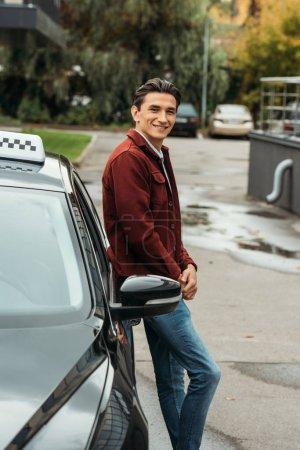 Photo pour Smiling taxi driver looking at camera beside car - image libre de droit