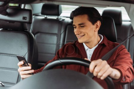 Photo for Smiling man looking at smartphone while driving car - Royalty Free Image