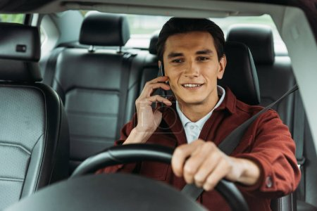 Photo for Smiling man talking at smartphone while driving car - Royalty Free Image