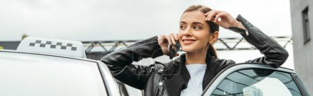 Photo for Smiling woman taxi driver talking on smartphone beside car, panoramic shot - Royalty Free Image