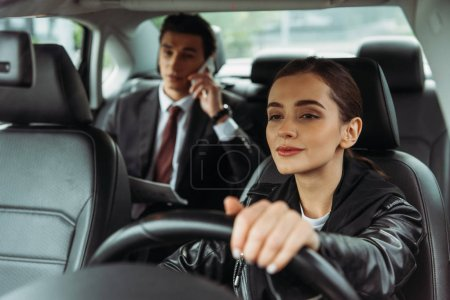 Photo for Woman taxi driver holding steering wheel while businessman talking on smartphone - Royalty Free Image