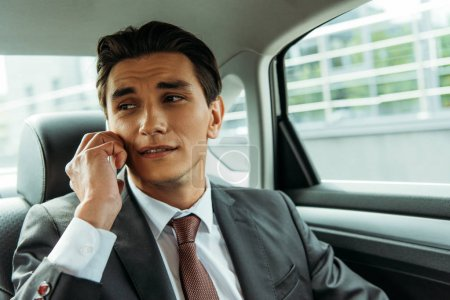 Photo for Handsome businessman talking on smartphone in taxi - Royalty Free Image