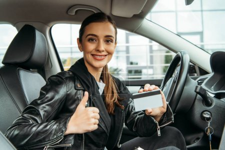 Photo for Smiling woman holding credit card and showing thumb up gesture in car - Royalty Free Image