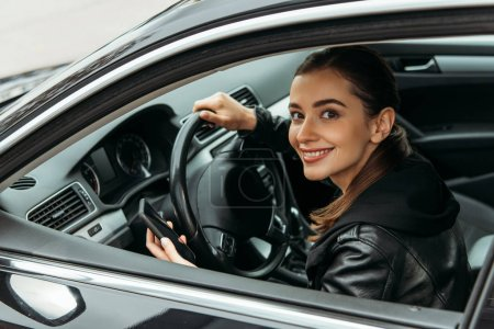 Photo for Smiling female taxi driver holding smartphone in car - Royalty Free Image