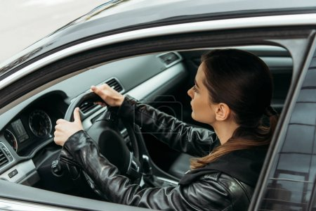 Photo for Side view of female taxi driver holding steering wheel - Royalty Free Image