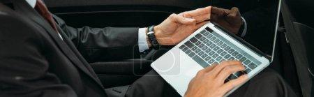 Foto de Vista recortada del hombre de negocios utilizando el ordenador portátil con pantalla en blanco en el coche, plano panorámico - Imagen libre de derechos