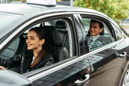 Photo pour Femme souriante chauffeur de taxi et homme d'affaires en voiture - image libre de droit