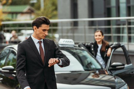 Photo for Selective focus of businessman looking at wristwatch and taxi driver by car - Royalty Free Image