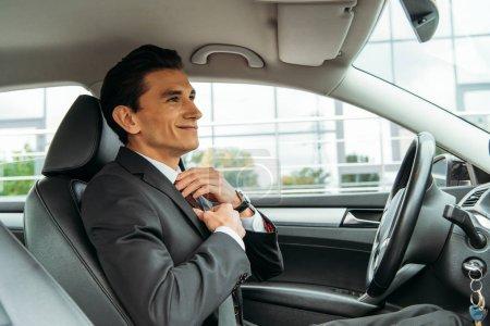 Photo pour Homme d'affaires souriant ajustant la cravate et regardant dans le miroir d'une voiture téléguidée - image libre de droit