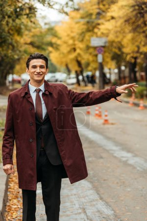 Photo for Smiling businessman catching taxi on street during autumn - Royalty Free Image