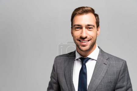 handsome and smiling businessman in suit looking at camera isolated on grey