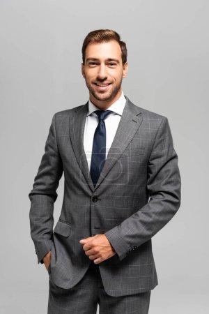 Photo pour Bel homme d'affaires souriant en costume regardant la caméra isolée sur gris - image libre de droit