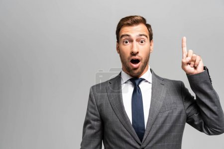 Photo for Handsome and shocked businessman in suit showing idea sign isolated on grey - Royalty Free Image