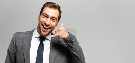Photo for Panoramic shot of smiling businessman in suit showing call me sign isolated on grey - Royalty Free Image