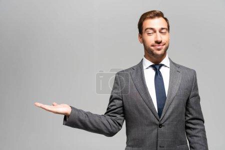 Foto de Maravilloso y sonriente empresario en traje apuntando con la mano aislada en gris. - Imagen libre de derechos