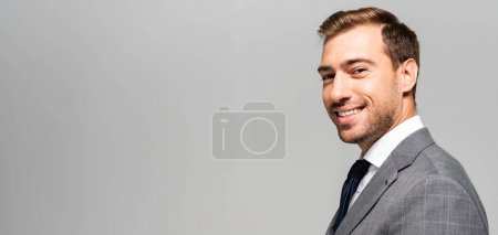 Photo for Panoramic shot of smiling and handsome businessman in suit looking at camera isolated on grey - Royalty Free Image