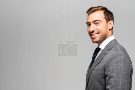 smiling and handsome businessman in suit looking at camera isolated on grey