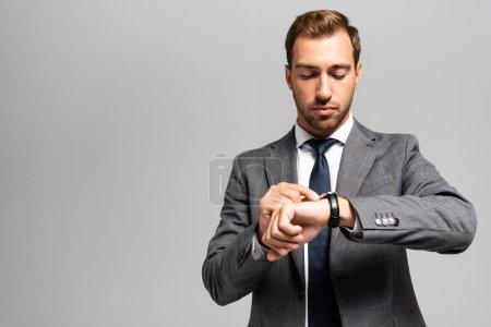 Photo pour Bel homme d'affaires en costume regardant une montre-bracelet isolée sur gris - image libre de droit
