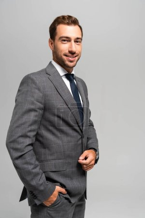 Photo for Handsome and smiling businessman in suit looking at camera isolated on grey - Royalty Free Image