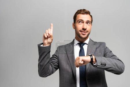 Photo pour Bel homme d'affaires souriant en costume montrant un signe d'idée isolé sur gris - image libre de droit