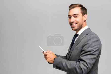 Photo for Smiling and handsome businessman in suit using smartphone isolated on grey - Royalty Free Image