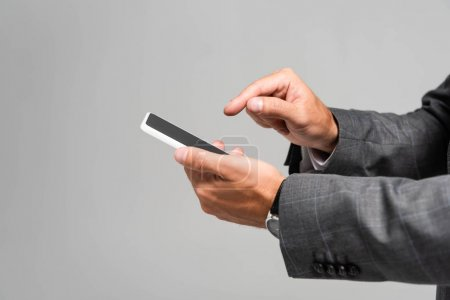 cropped view of businessman in suit pointing with finger at smartphone isolated on grey