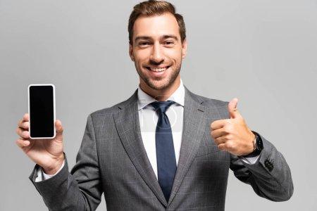 Photo pour Homme d'affaires souriant en costume tenant smartphone et montrant comme signe isolé sur gris - image libre de droit