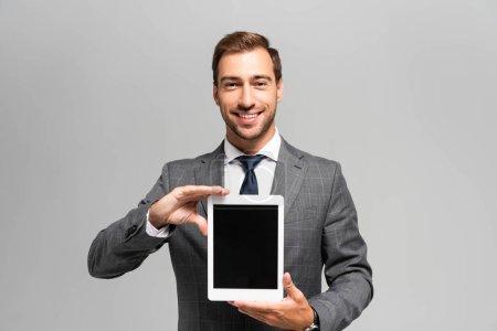 Photo pour Homme d'affaires beau et souriant en costume tenant tablette numérique isolé sur gris - image libre de droit