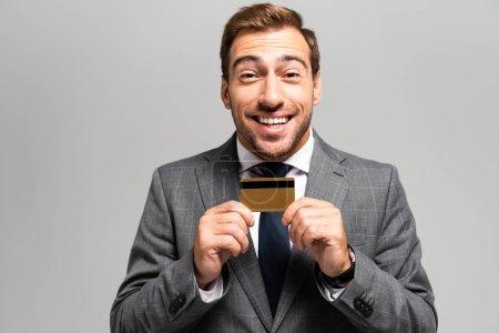 Photo pour Bel homme d'affaires souriant en costume tenant une carte de crédit isolée sur gris - image libre de droit