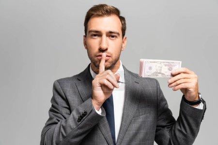 Photo pour Bel homme d'affaires en costume montrant un geste shh et tenant des billets de dollars isolés sur le gris - image libre de droit