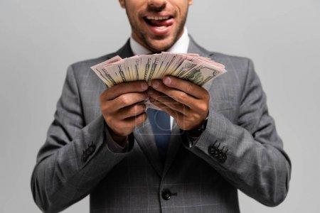 Foto de Vistas recortadas de hombres de negocios con traje que tienen billetes de banco en dólares y labios que lamen aislados en gris. - Imagen libre de derechos